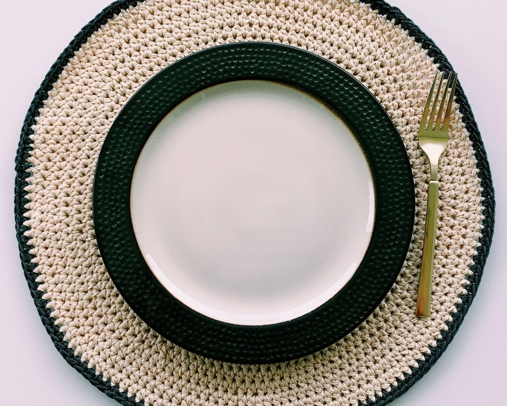 round crochet placemat pattern with decorative plate and fork